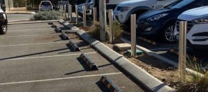 steel bollards in a parking lot with parked cars